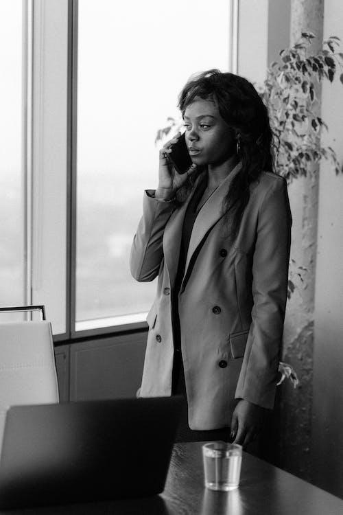 Woman in Coat Standing Near Window