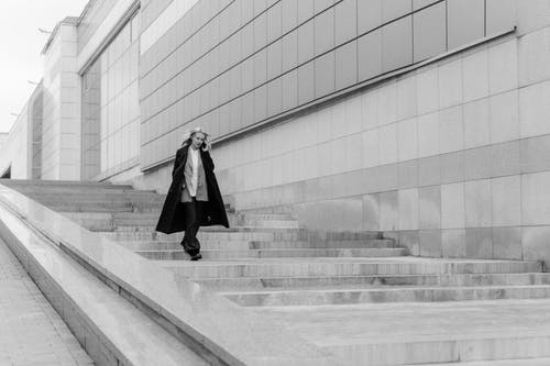 Woman in Black Coat Standing on White Concrete Stairs