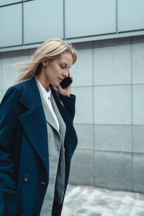 Woman in Blue Blazer Standing Near White Wall