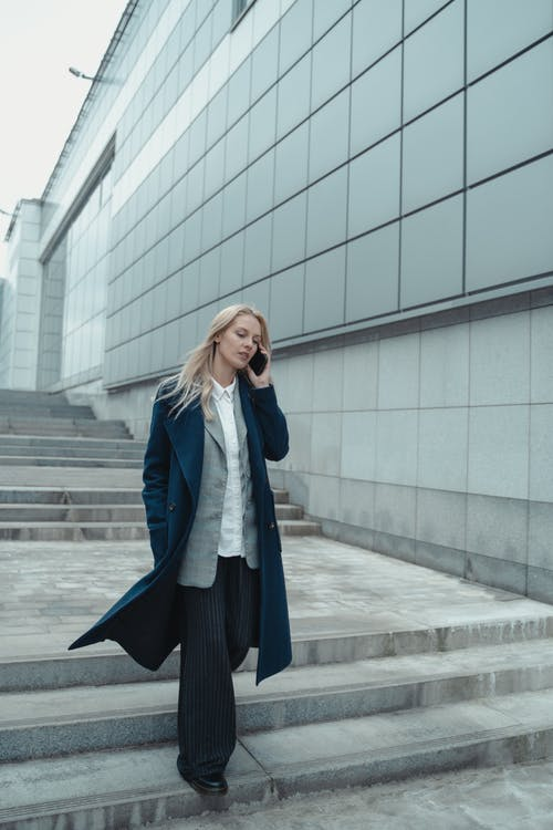 Woman in Blue Coat Standing Near White Concrete Building