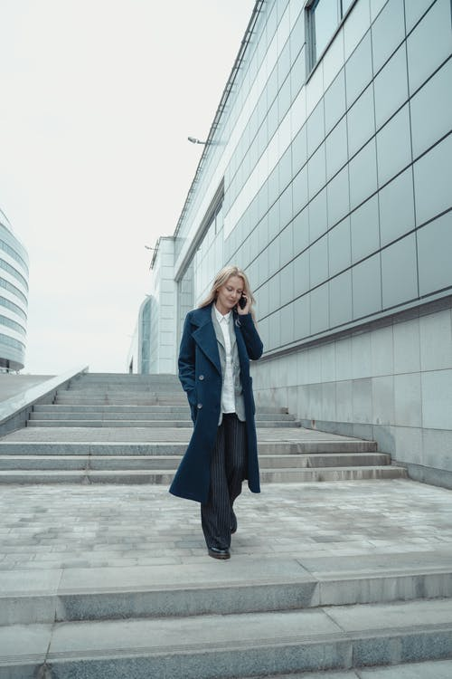 Woman in Blue Blazer and Black Skirt Standing on Gray Concrete Floor
