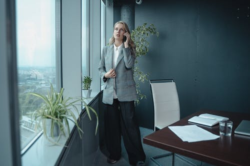 Woman in Gray Blazer Standing Near Glass Window