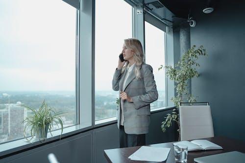 Woman in Gray Blazer Standing Near Window