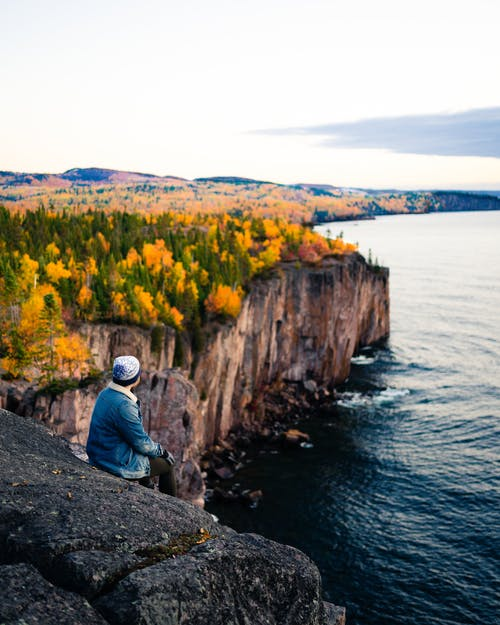 Traveling man sitting alone on edge of high cliff observing autumn woods and calm sea