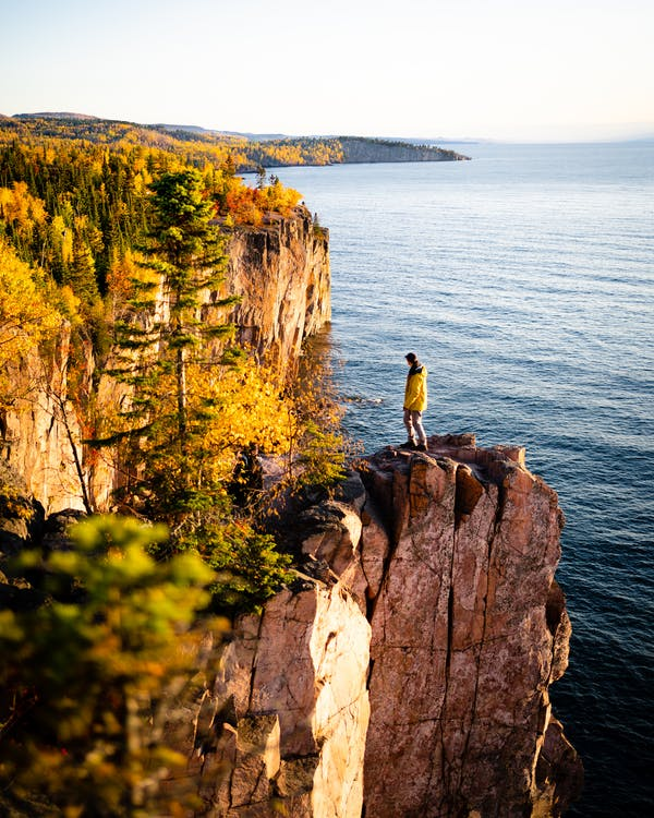 Person on rocky cliff in autumn sunlight