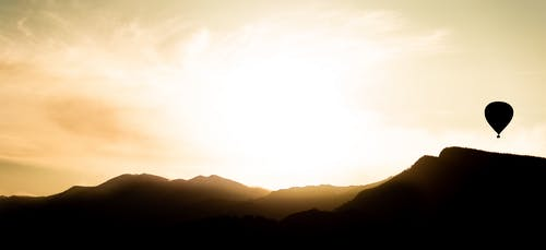Panorama with silhouette of mountains and flying air balloon against glowing sky at sunset