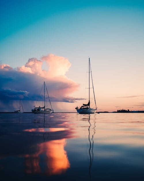 Tranquil smooth surface of sea reflecting sunset sky and yachts floating in twilight