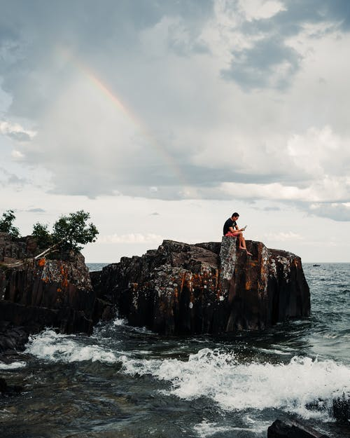Distant person sitting on rocky cliff above rolling waves on seashore under rainbow