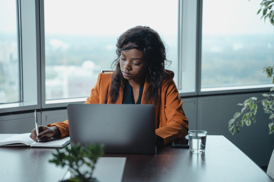 Woman in Orange Jacket Using Macbook