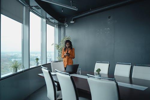 Woman in Orange Shirt Sitting on Chair