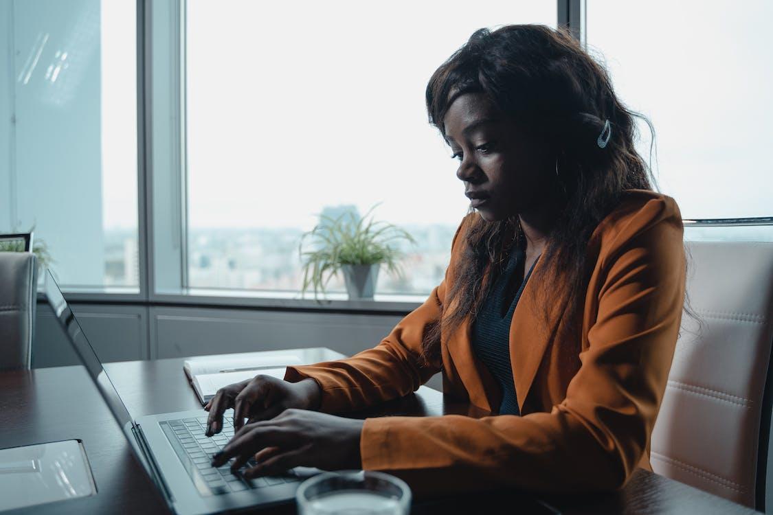 Woman in Brown Long Sleeve Shirt Using Laptop Computer