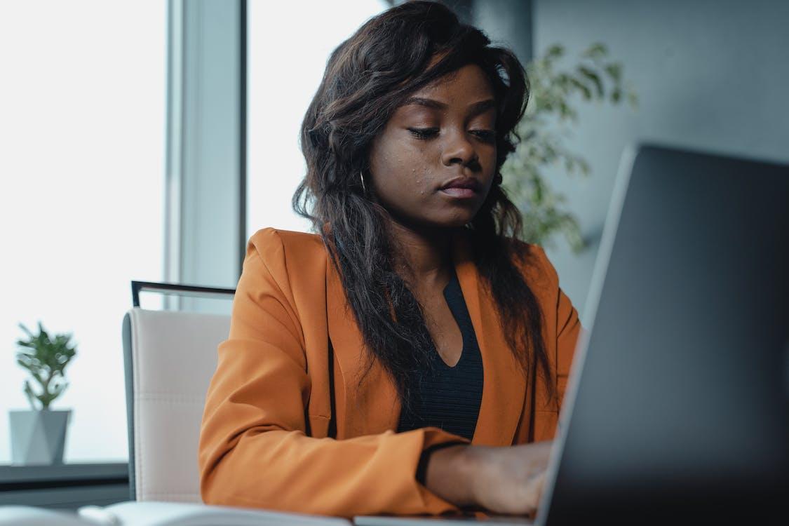 Woman in Orange Blazer Using Laptop Computer