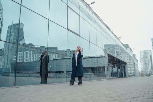 Man in Blue Suit Standing Near Glass Building