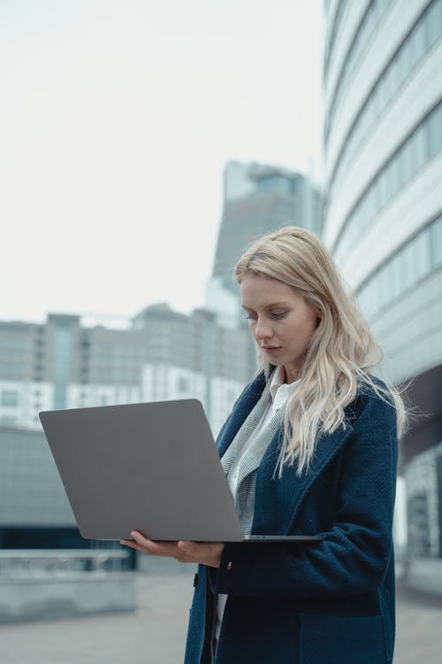Woman in Blue Blazer Using Macbook