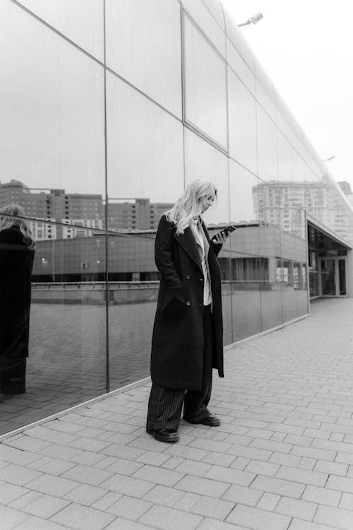 Woman in Black Coat Standing on Sidewalk