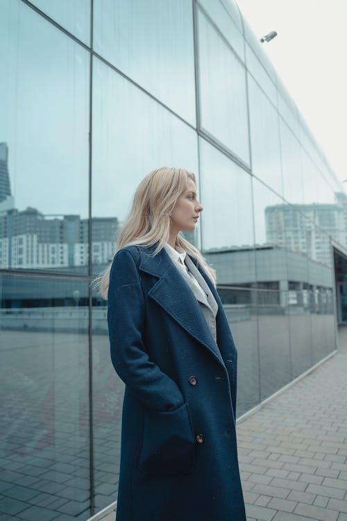Woman in Blue Blazer Standing Near Glass Building