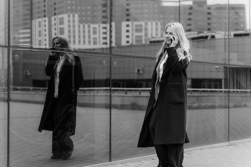 Grayscale Photo of Woman in Coat Standing Beside Man in Black Coat