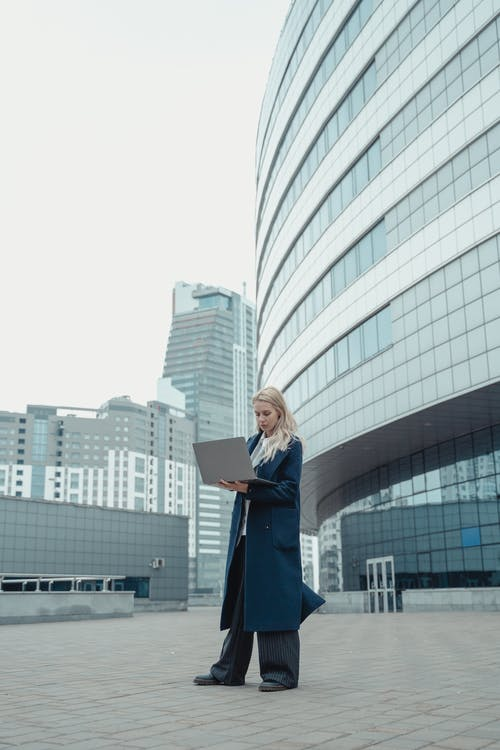 Woman in Blue Coat Standing Near White Building