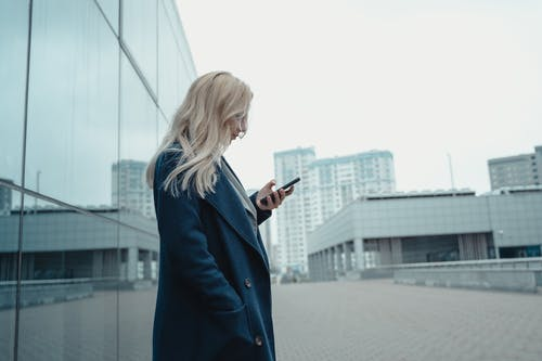 Woman in Blue Long Sleeve Dress Holding Smartphone