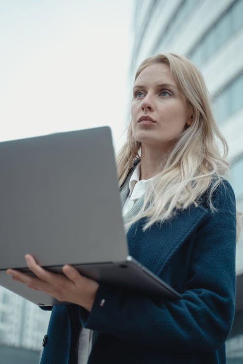 Woman in Blue Sweater Holding Black Tablet Computer