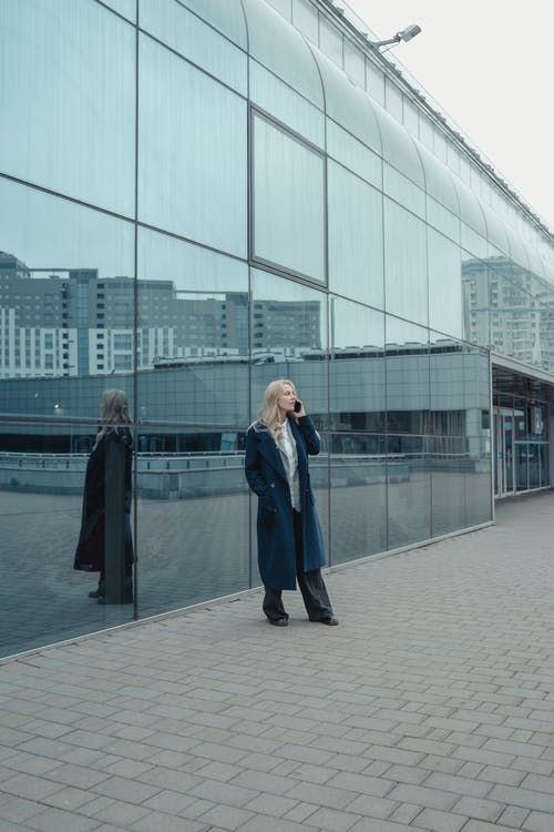 Woman in Blue Coat Standing on Gray Concrete Floor