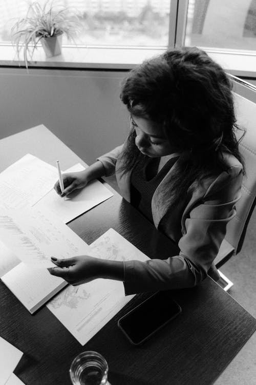 Woman in Long Sleeve Shirt Writing on White Paper