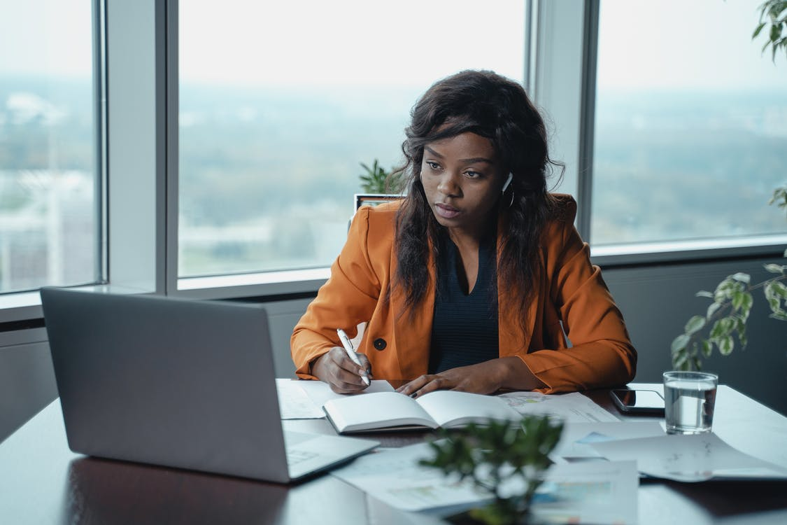 Woman in Brown Blazer Sitting by the Table Using Macbook
