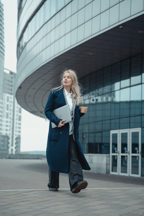Woman in Blue Blazer Standing Near White Building