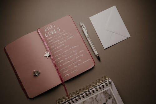 Pink Notebook Beside White Click Pen