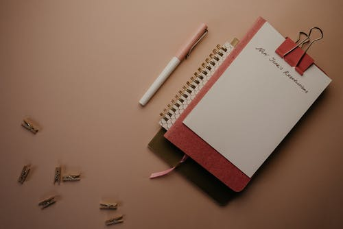 White and Pink Click Pen Beside White Notebook