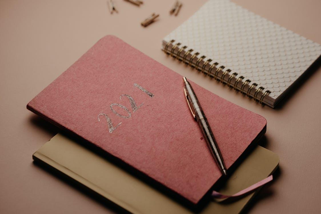 粉色笔记本上的银色和黑色点击笔