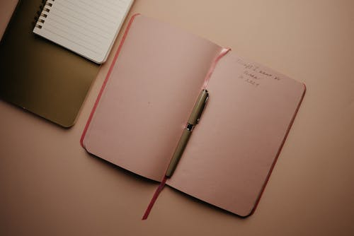 Pink Notebook With Pen on White Table