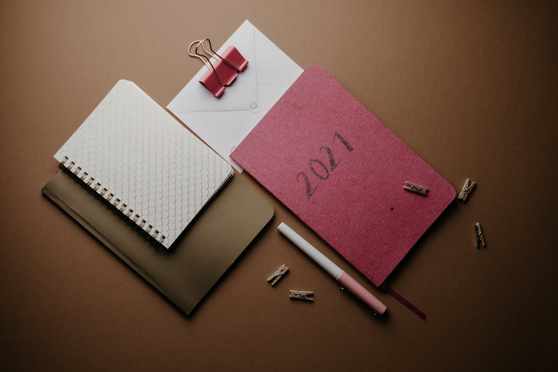 Pink and White Spring Notebook Beside White Click Pen