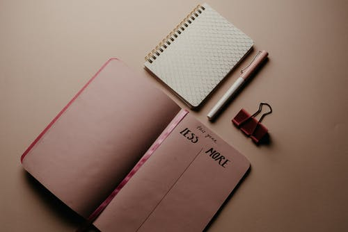 Pink and White Notebook Beside Black and Red Headphones
