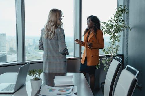 Woman in Brown Coat Standing Beside Woman in Gray Coat