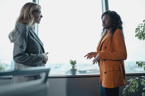Woman in Gray Blazer and Orange Dress Standing Beside Window