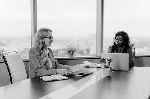 Woman in Gray Long Sleeve Shirt Sitting Beside Woman in Gray Long Sleeve Shirt