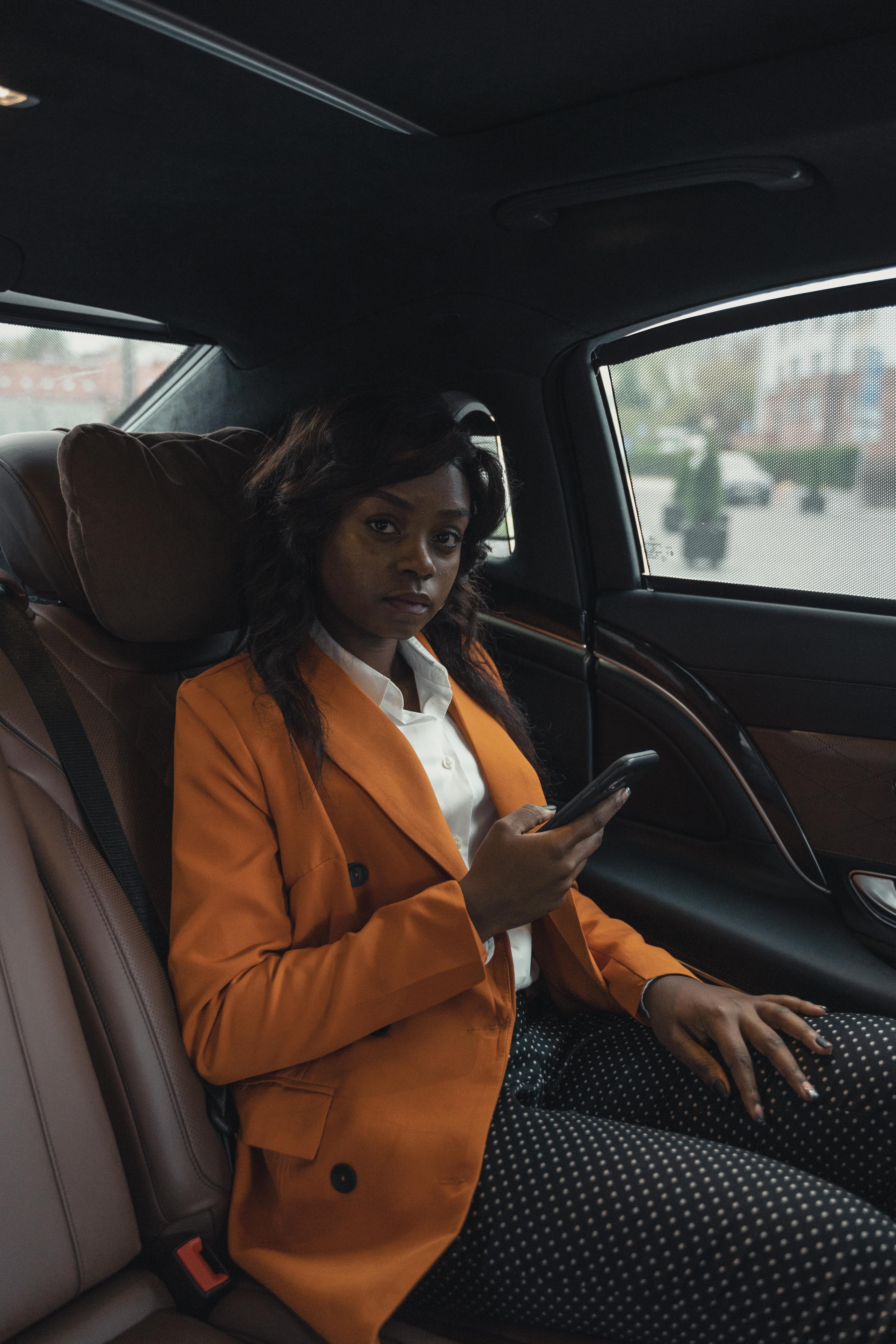 woman in orange blazer sitting on car holding her phone