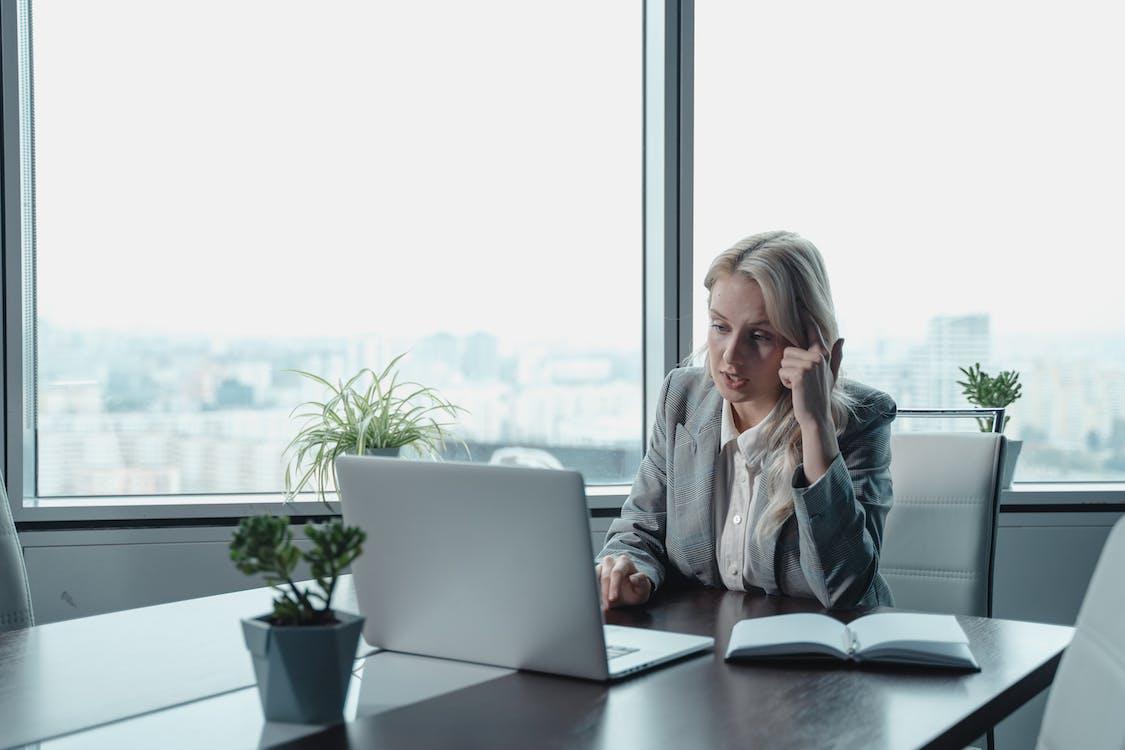 Woman in Gray Long Sleeve Shirt Sitting Beside Black Laptop Computer