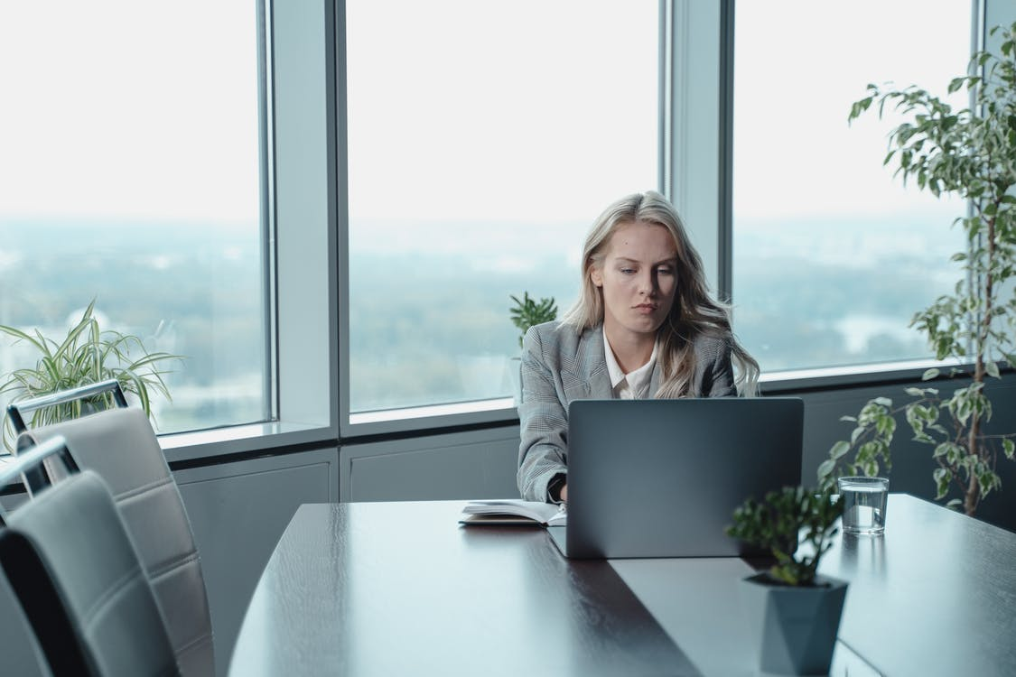 Woman In Gray Blazer Sitting On Chair Using Laptop