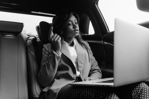 Grayscale Photo Of Woman Sitting Inside A Car