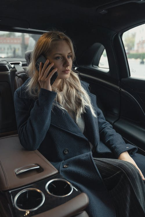 Woman Wearing A Coat Sitting Inside A Car