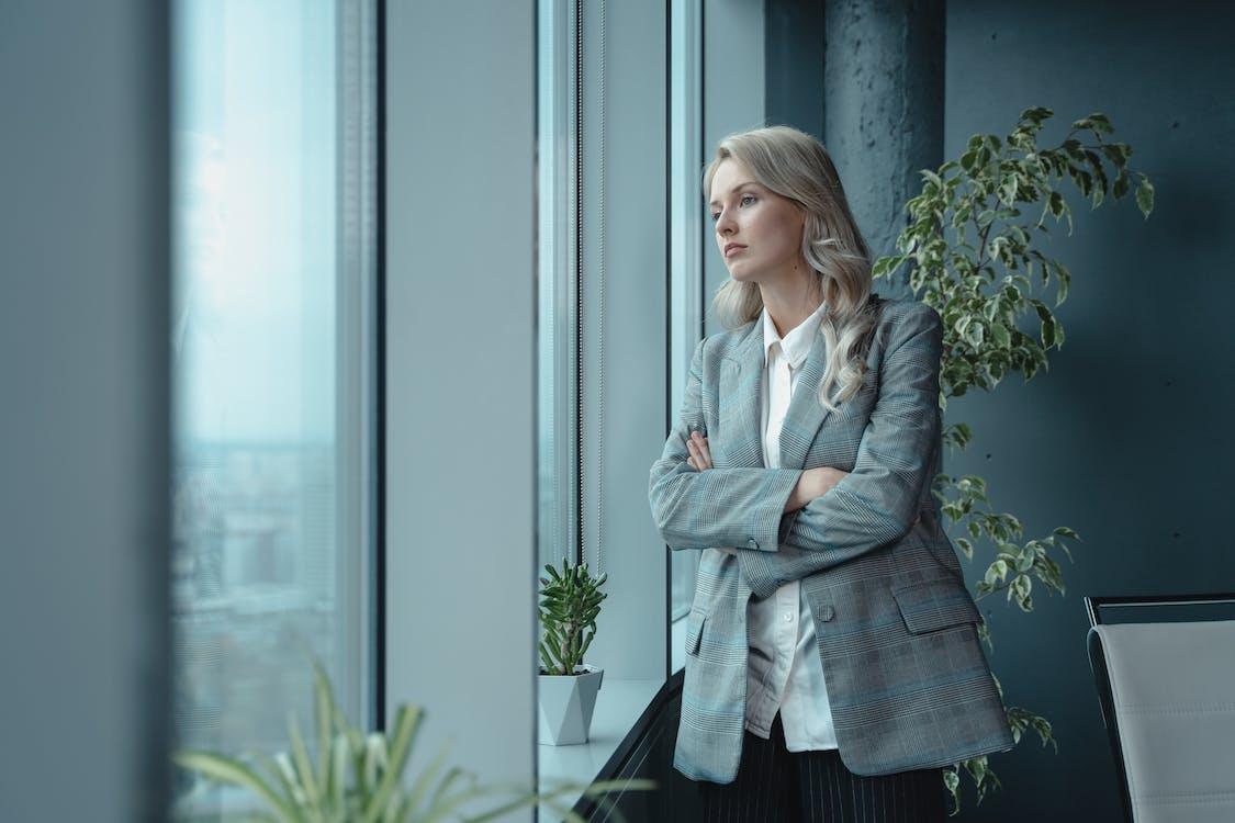 Woman In Gray Coat Standing Beside Glass Window