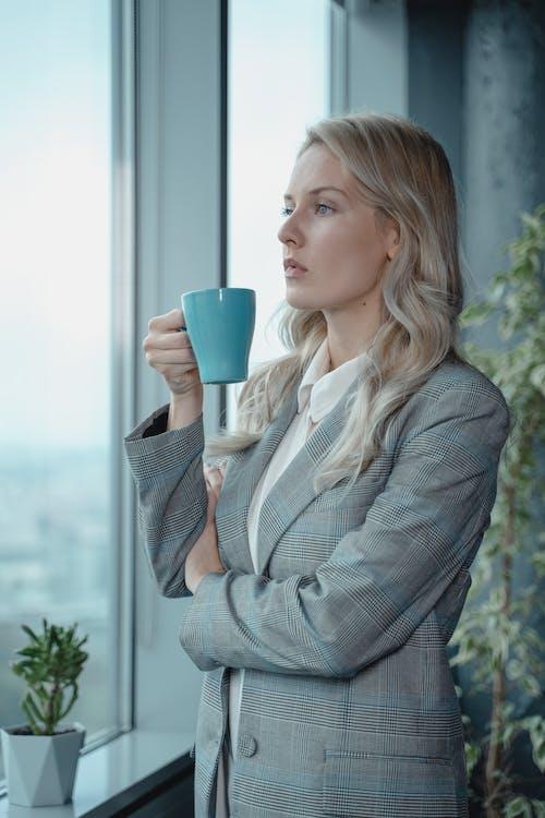 Woman In Gray Blazer Holding Blue Ceramic Mu