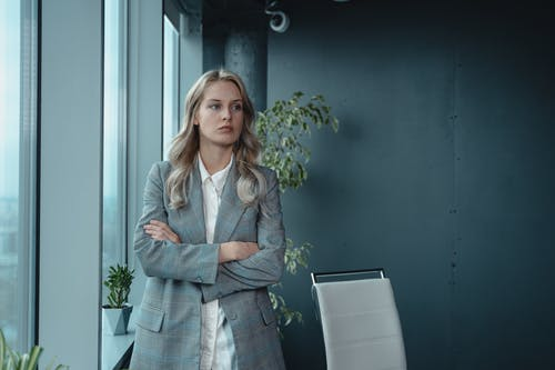 Woman In Gray Blazer Standing By The Window