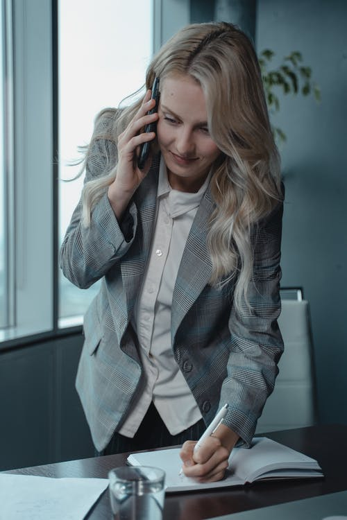 Woman In Gray Blazer Holding Phone To Her Ear