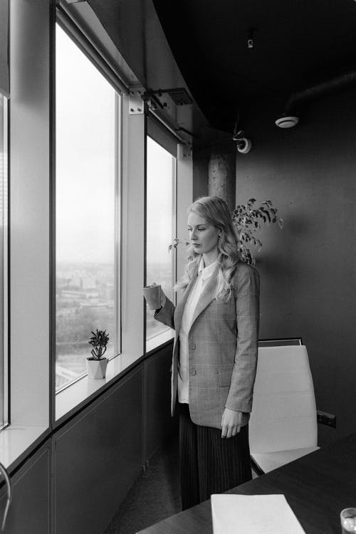 Woman In A Blazer Standing Beside Window