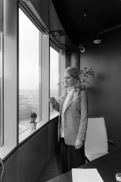 Woman In A Blazer Standing Beside Window