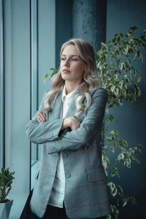 Woman in Gray Blazer Standing Near Green Plant With A Serious Look
