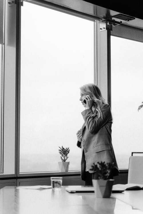 Grayscale Photo Of Woman In Long Sleeve Shirt Standing Beside Window